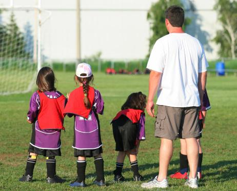 Kids with coach on soccer field