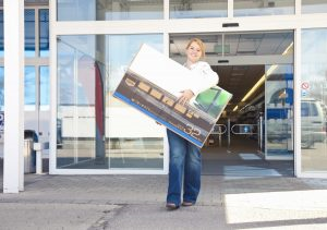 Woman carrying TV out of store