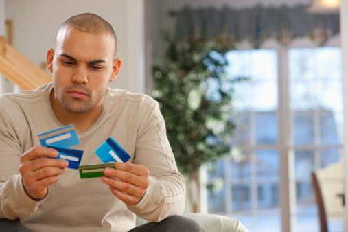 Young Man holding 4 Credit Cards