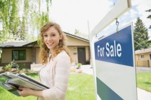 "Realtor in front of ""for Sale"" sign"
